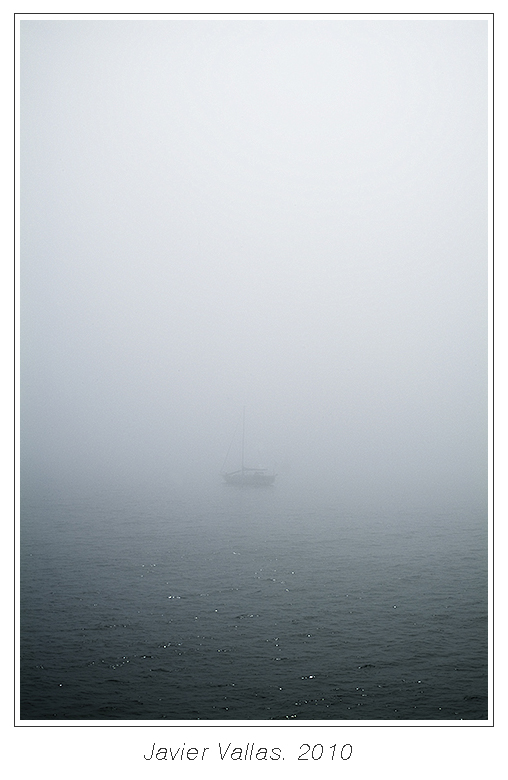 Fotografía del océano atlántico en el que podemos ver a un barco difuminado a lo lejos en la niebla