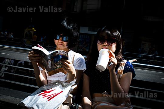 Fotografía de dos mujeres orientales sentadas en la Gran Vía de Madrid (España)
